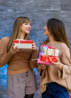 ギフトボックスを保持している2人の女の子。新年またはクリスマスまたは誕生日のお祝い。プレゼントを贈る