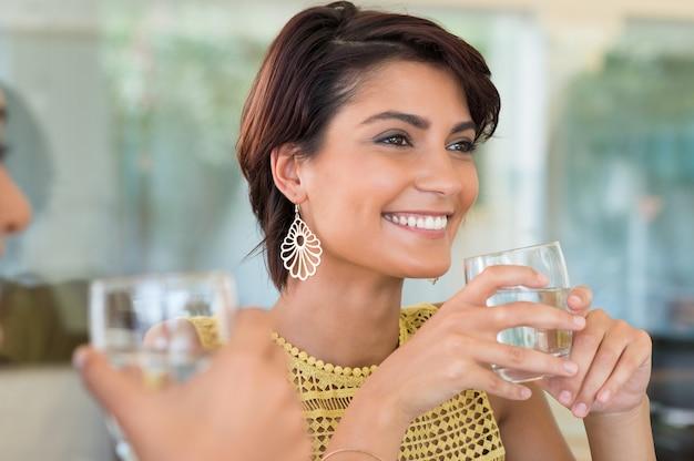 手に水のガラスを保持している2人の女の子