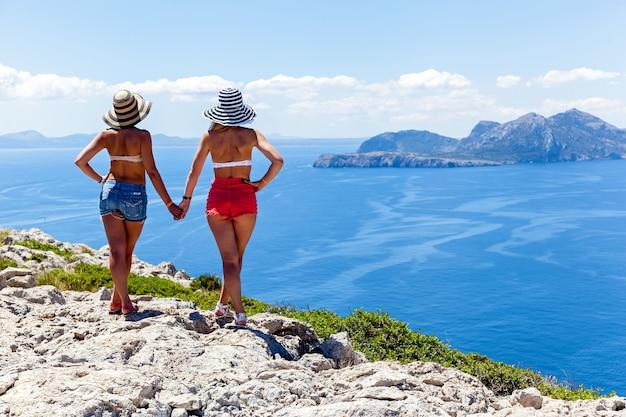 手をつないでいる2人の女の子が美しい海の景色を眺める、岩の端にいる女の子