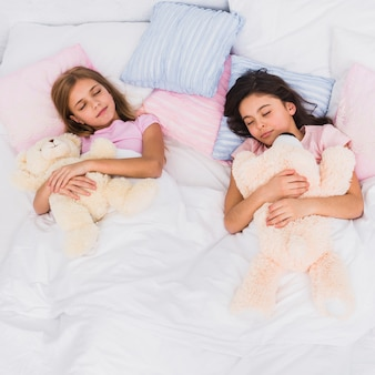 Two girls holding teddy bear in hand sleeping together on bed