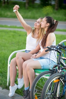 Two girls in a bench with bikes