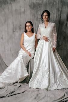 Две девушки в свадебном платье студийный портрет на сером фоне