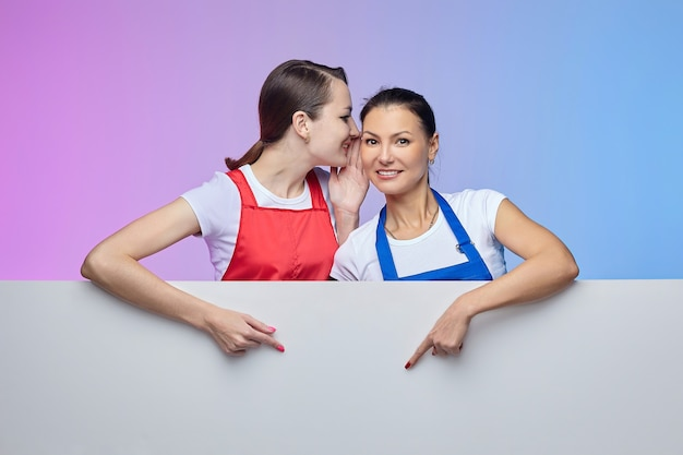 エプロンを着た2人の女の子が白い看板でポーズをとる。広告の概念