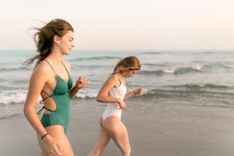 Две девушки в бикини, идущие рядом с морем на пляже