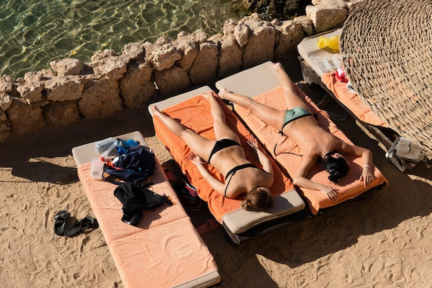 홍해를 배경으로 일광욕 용 라운 저에서 일광욕을하고있는 비키니 입은 두 소녀.
