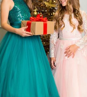 세련된 드레스를 입은 두 소녀가 크리스마스 트리 앞에 서 있습니다.