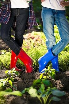 夏の暑い日に庭のベッドでポーズをとるカラフルな長靴を履いた 2 人の女の子