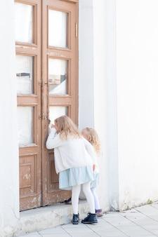 드레스를 입은 두 소녀가 거리에서 문 밖을 들여다보고 있습니다. 호기심 많은 아이들