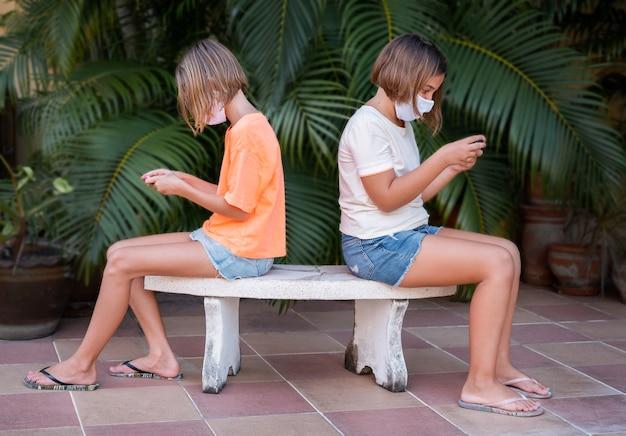 Две девушки в маске сидят на скамейке и играют в телефоны