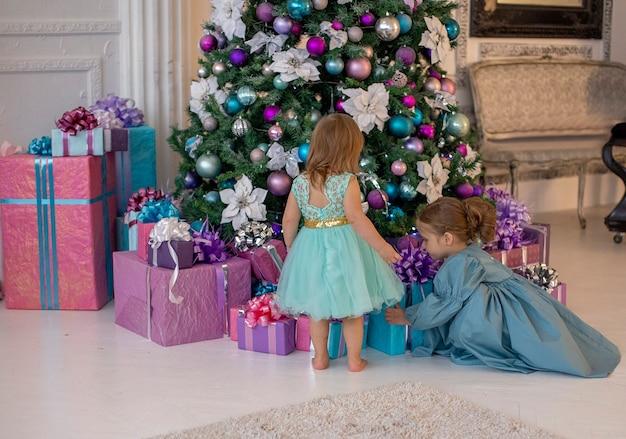 派手なドレスを着た2人の女の子が、美しく装飾された木の下でクリスマスプレゼントを探しています