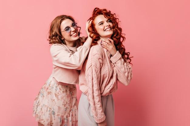 ピンクの背景にポーズをとって機嫌の良い2人の女の子。幸せを表現するトレンディな女性のスタジオショット。
