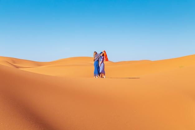 Две девушки в платках в пустыне сахара.