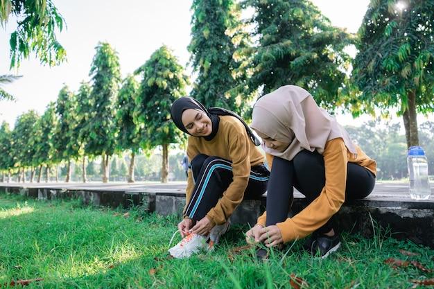 公園で一緒に午後の運動の準備のために靴ひもを持ってチャットしながらスカーフの2人の女の子