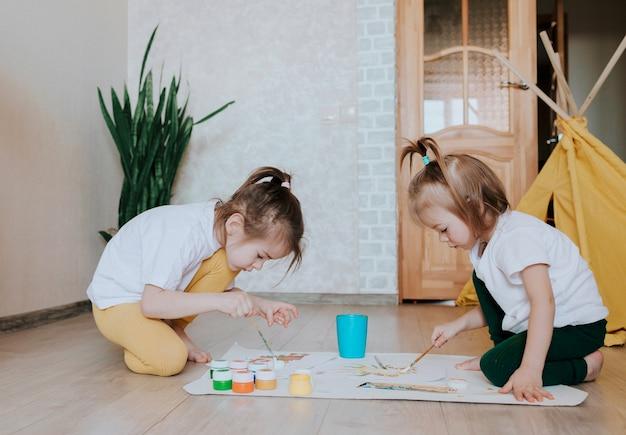 밝은 색의 옷을 입은 두 소녀가 무릎을 꿇고 앉아 밝은 수채화로 열정적으로 그림을 그립니다.