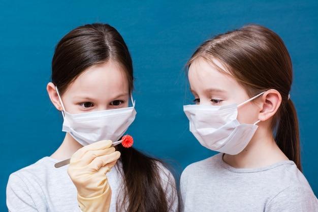 医療用マスクを着た2人の女の子が、1人がピンセットで保持しているコロナウイルスを調べています。ラテックスの手袋をはめてください。肺炎のパンデミック