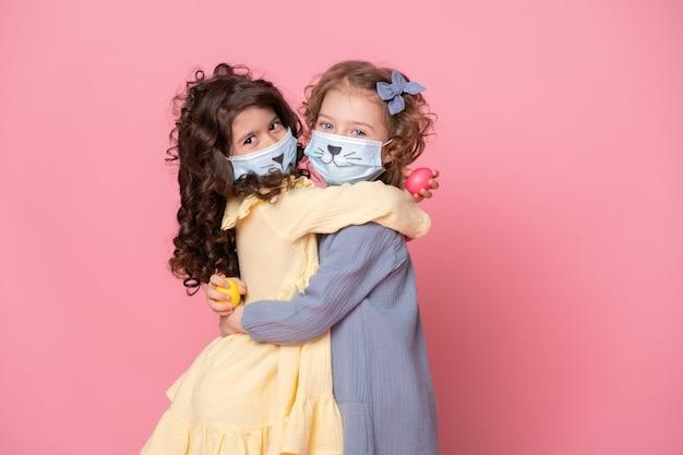Две девушки в защитной маске с крашеными яйцами на розовом фоне. covid пасхальная концепция.
