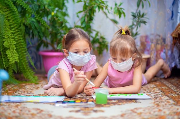 保護用医療マスクの2人の女の子が自宅の床に横たわっている塗料でペイント