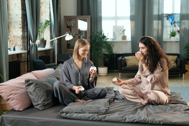 シルクのパジャマ姿の2人の女の子が、手に天然の手作り化粧品を塗り、朝のベッドに座ってその香りを楽しんでいます。