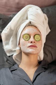 シルクのパジャマを着た2人の女の子、頭にタオル、顔に粘土のマスク、目を閉じてキュウリのスライスをベッドに横になり、美容の手順を楽しんでいます