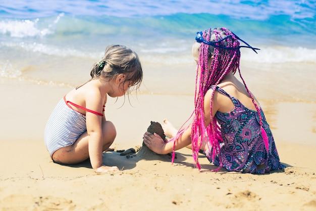 바다에서 모래에서 노는 수영복을 입은 두 소녀 그들 중 한 명은 분홍색 땋은 머리를 땋고 있습니다