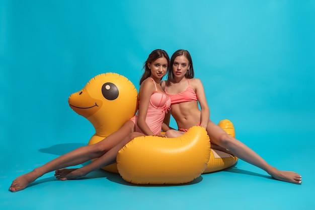 파란색 벽에 풍선 오리에 포즈 수영복에 두 여자