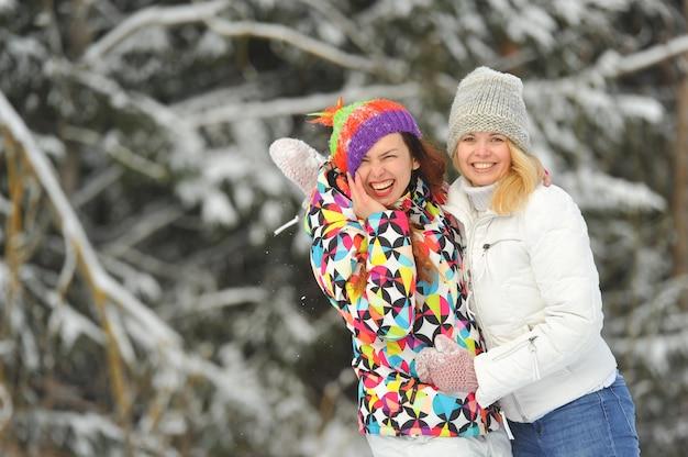 Две девушки в зимнем лесу эмоционально обнимаются и улыбаются. счастливые женщины обнимаются и выражают радость