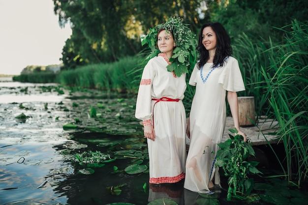 Две девушки в традиционной утренней одежде в воде