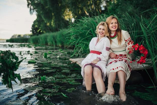 Две девушки в традиционной утренней одежде смеются в воде