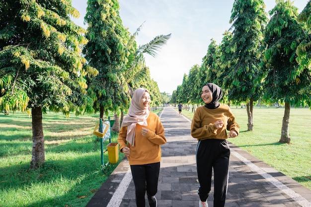 ベールに身を包んだ二人の女の子が庭で一緒にジョギングしながらアウトドアスポーツをする