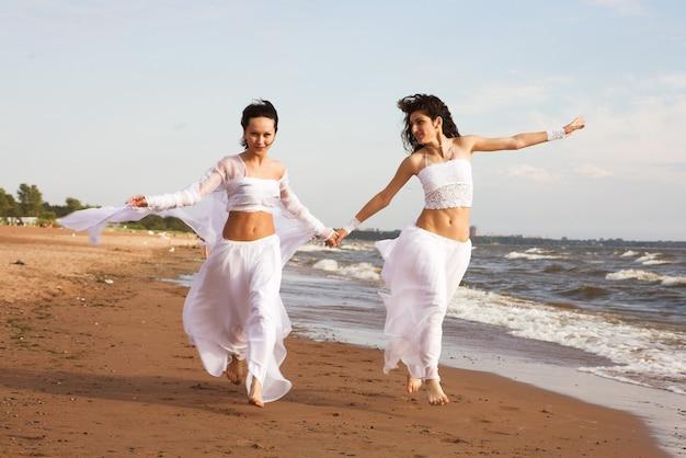 Две девушки в белом платье танцуют на берегу моря