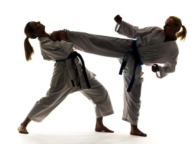 Две девушки в белых кимоно с черными и синими поясами, тренируются и практикуют стойки и техники карате