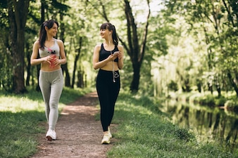 Two girls jogging in park