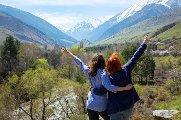 Two girls joyfully raise their hands up , summer mountains