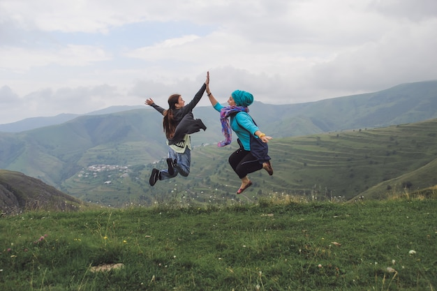 Two girls jumping in the air and clap their hands in mountains