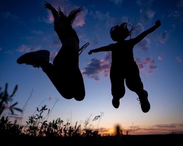 二人の女の子が夕焼けの夕焼け空、影をジャンプ