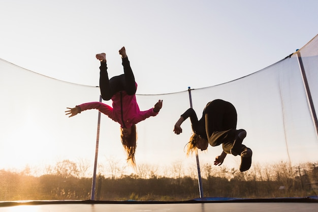 Two girls jumping on trampoline at sunset