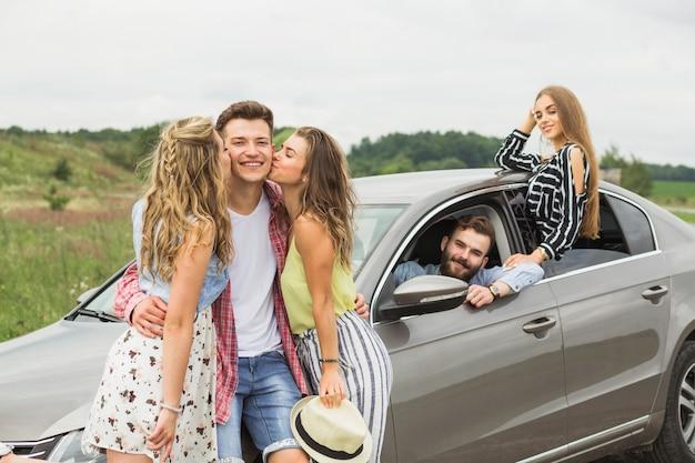 Two girls kissing her boyfriend standing near the car