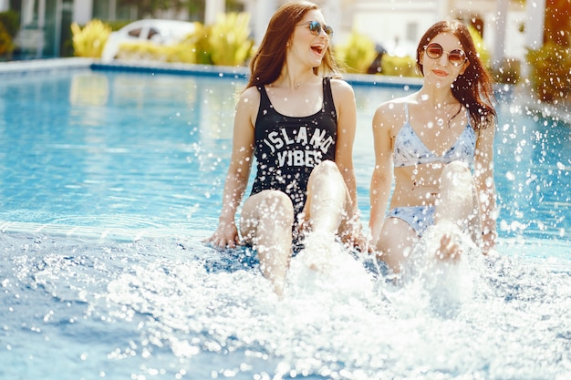 Two girls laughing and having fun by the pool