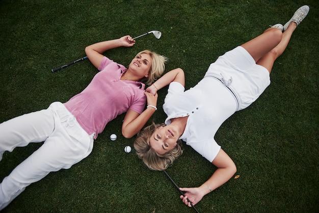 두 여자는 골프 코스에 누워 게임 후 휴식