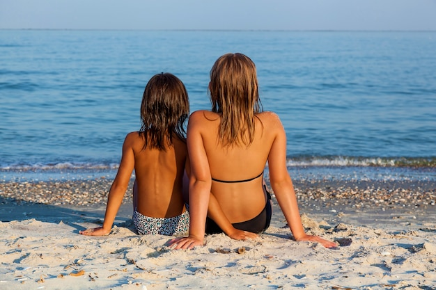 두 소녀의 여동생이 해변에 앉아 푸른 물을 바라보며 태양을 즐기고 있습니다. 여름 방학