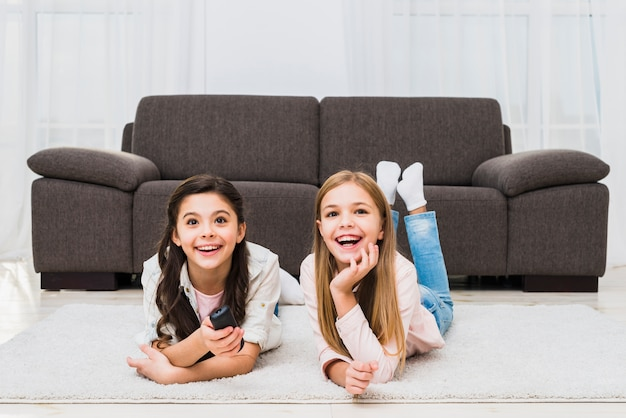 Two girls lying on carpet enjoying watching the television