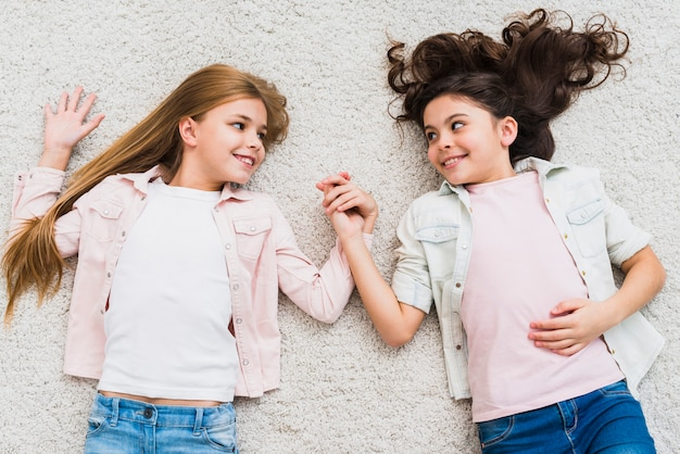 Two girls lying on white carpet holding hand looking at each other