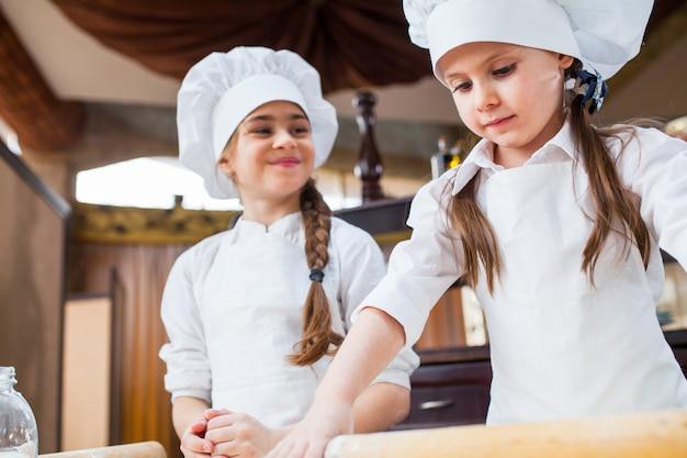 Two girls make flour dough.