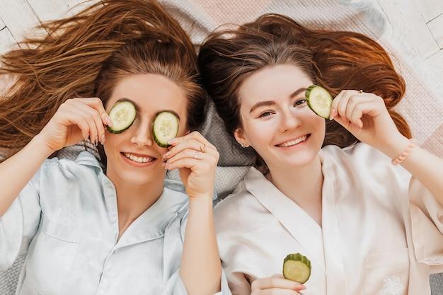 Две девушки делают домашние косметические маски для лица и волос. огурцы для свежести кожи вокруг глаз. женщины заботятся о молодой коже. подруги смеются дома, лежа на полу на подушках.