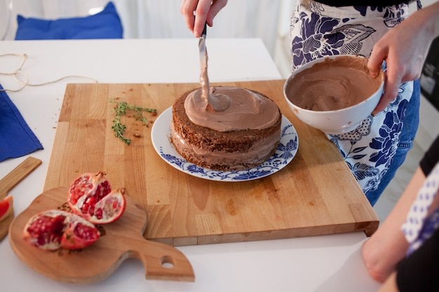 キッチンでケーキを作る2人の女の子。女性の手、チョコレートクリームの原因