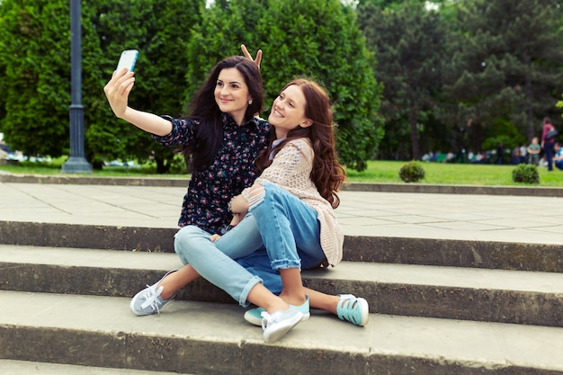 Two girls making funny selfie on the street, having fun together