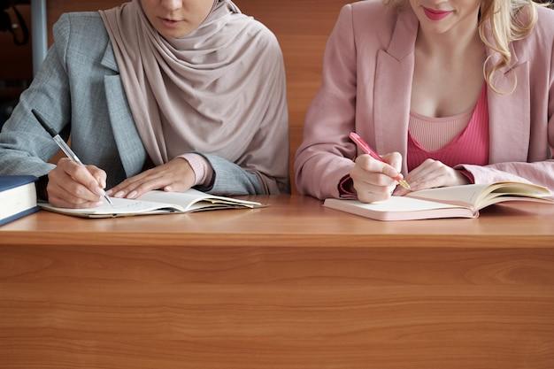 책상 옆에 앉아 메모를 하는 두 소녀