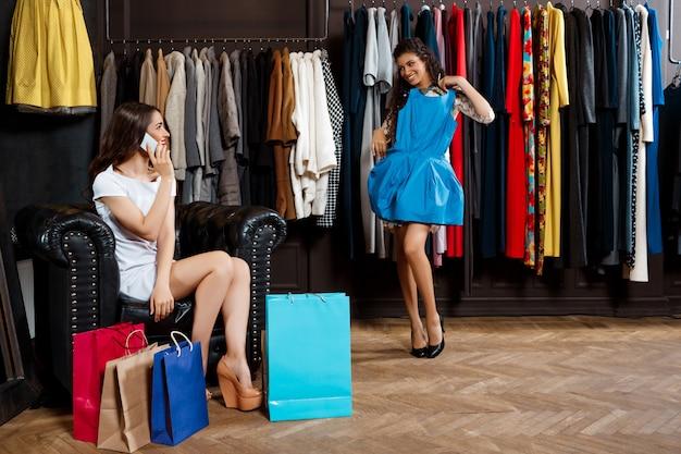 쇼핑몰에서 쇼핑을하는 두 여자. 하나는 전화로 말하기.