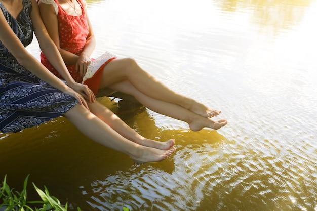 ヴィンテージのドレスを着た川の近くの2人の女の子。休日を楽しんでいる裸足の女性。素朴な夏のフラットレイ。友達のライフスタイルのコンセプト。木製の橋。