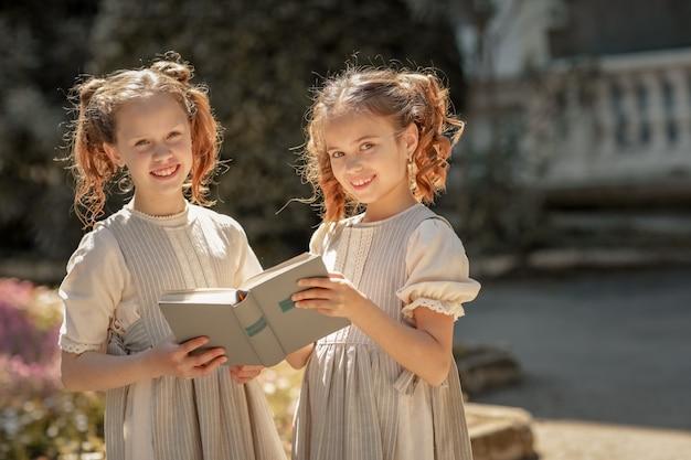 小学校の中学生の二人の少女がアカデミーの中庭で本を読んだ。